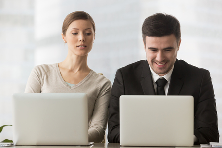 Photo pour Interested curious corporate spy looking at colleagues laptop, spying on rival, cheating on examination, stealing idea, sneaking peek, taking inquisitive glance at computer screen of unaware coworker - image libre de droit