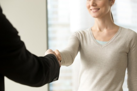 Foto de Smiling businesswoman shaking businessman hand standing in office, friendly welcome gesture, thanking for help, greeting new client, nice to meet you handclasp, focus on handshake, close up view - Imagen libre de derechos