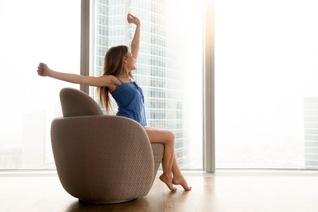 Young positive woman sitting and stretching in armchair near big bright window in hotel room. Relaxed lady feeling good in morning at home, enjoying start of new wonderful vacation day after waking up