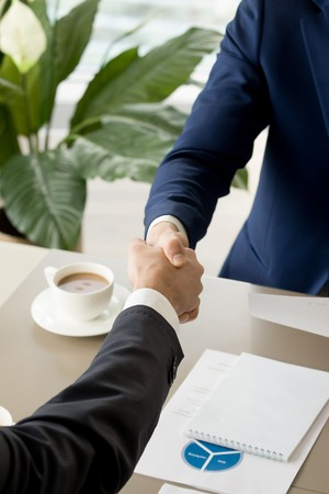 Photo pour Close up image of businessmen handshake over desk with coffee cup and business documents. Business partners showing trust during negotiation, welcoming on meeting, confirming deal with shaking hands - image libre de droit