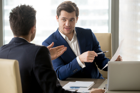Photo pour Successful businessman clarifying provisions of contract with business partner, discussing terms of agreement, explaining strategy or financial plan. HR manager asking job candidate about his resume - image libre de droit