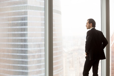 Concerned or serious businessman in expensive suit standing in office, looking outside the window at modern city building, contemplating risky financial projects, worrying about upcoming business deal
