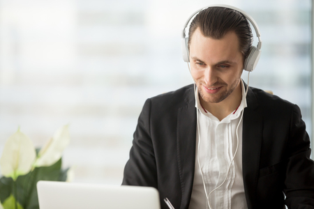 Photo pour Smiling businessman in headphones looking at laptop screen at workplace. Friendly young manager participating in online meeting or conference, remote job interview, learning foreign languages. - image libre de droit