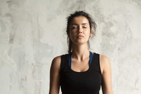 Photo pour Portrait of young attractive yogi woman with her eyes closed in meditating pose, relaxation exercise, working out, wearing sportswear, black top, indoor close up image, wall background - image libre de droit