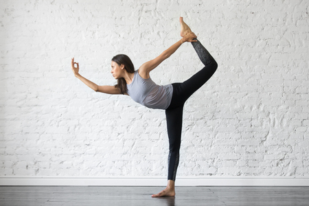 Foto de Young attractive woman practicing yoga, stretching in Natarajasana exercise, Lord of the Dance pose, working out, wearing sportswear, gray tank top, black pants, indoor full length, studio background - Imagen libre de derechos