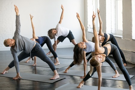 Foto de Group of young sporty people practicing yoga lesson with instructor, standing in Trikonasana exercise, extended triangle pose, working out indoor, full length studio. Wellbeing, wellness concept - Imagen libre de derechos