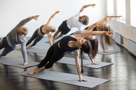 Photo pour Group of young sporty people practicing yoga lesson with instructor, stretching in Bending Side Plank exercise, Vasisthasana pose, working out, indoor studio image. Wellbeing, wellness concept - image libre de droit