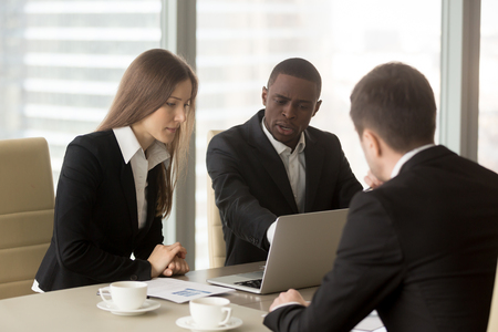 Photo pour Group of multinational financiers working together on company strategy, planning financial results, examining marketing researches. Black businessman consulting with caucasian colleagues in office - image libre de droit