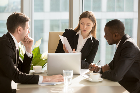 Foto de Confident caucasian businesswoman showing document with financial indicators, presenting project to african american colleague during negotiations in meeting room at office. Planning business strategy conference table - Imagen libre de derechos
