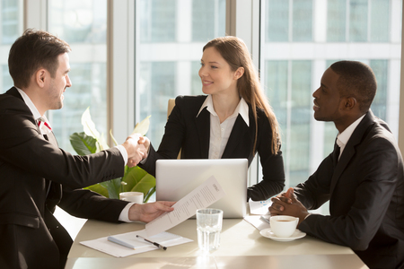 Photo pour Happy female company leader sitting at desk with her african american partner, shaking hand with satisfied businessman after successful negotiations and contract conclusion. International cooperation - image libre de droit