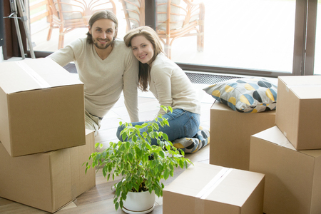 Photo pour Moving day, happy couple looking at camera sitting on the floor bonding with boxes belongings, young first time homeowners enjoying new home, buying real estate, move in out and relocation concept - image libre de droit