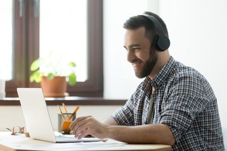 Photo for Handsome man with beard listening music in headphones and looking on screen of laptop. Young manager having a rest and playing in computer games or making video call on pc - Royalty Free Image