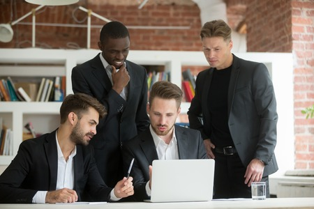 Executive multiracial team in suits brainstorming on project looking at laptop screen, diverse businessmen discuss new idea with computer together at office meeting, multi-ethnic group talk teamwork