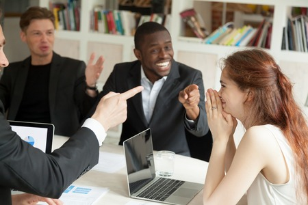 Foto de Happy executive businesswoman feels shy at corporate office meeting while male colleagues congratulating supporting success win pointing fingers at coworker, achievement at work, employee recognition - Imagen libre de derechos
