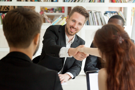 Photo pour Smiling businessman and businesswoman shaking hands sitting at meeting table, new partners greeting making first impression starting group negotiations teamwork, satisfied entrepreneurs handshaking - image libre de droit