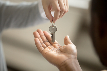 Photo pour Realtor woman giving african american customer hand taking key, black man buyer house owner purchasing new home, mortgage loan investment contract, buying real estate deal concept, close up view - image libre de droit