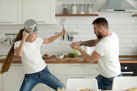 Foto de Funny couple pretending fight with utensils tools while cooking at home together, husband and wife having fun feeling playful holding kitchenware struggling in the kitchen preparing healthy food - Imagen libre de derechos