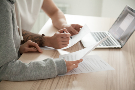 Couple reading legal documents at home with laptop, family considering mortgage loan or insurance, studying contract details, discussing terms and conditions, close up view of hands holding papers
