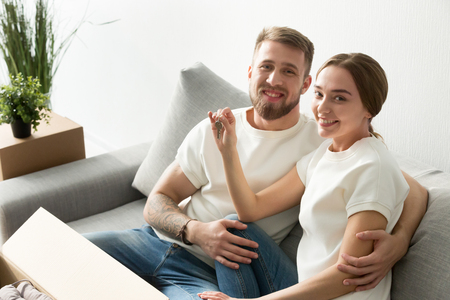 Smiling homeowners married couple holding house keys looking at camera sitting on sofa with boxes moving in new apartment, happy buyers made real estate deal, property ownership concept, portrait