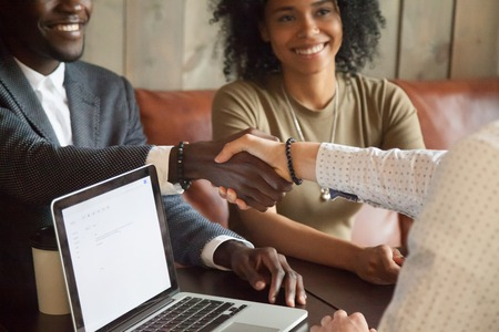 Photo pour Happy young african american couple making deal handshaking caucasian insurance broker in cafe, black satisfied customer and realtor or sales person shaking hands at meeting in office with laptop - image libre de droit