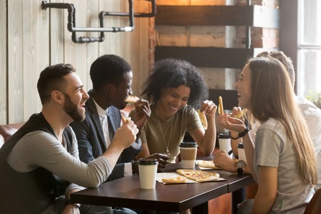 Photo pour Multiracial happy young people eating pizza in pizzeria, black and white cheerful mates laughing enjoying meal having fun sitting together at restaurant table, diverse friends share lunch at meeting - image libre de droit