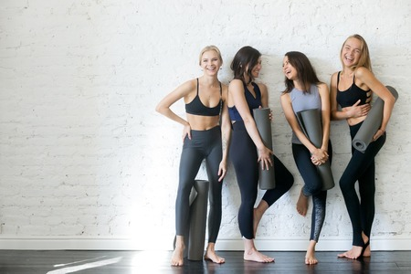 Group of young sporty girls with yoga mats standing at white wall.