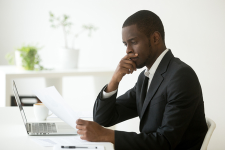 Serious african-american businessman employer thinking of business offer reading mail cover letter at workplace, puzzled black company executive looking at financial document considering contract