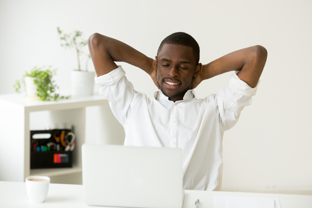 Photo pour Satisfied happy attractive african american man relaxing hands behind head with coffee and laptop having break at home office desk, black relaxed businessman enjoying pleasant good morning at work - image libre de droit