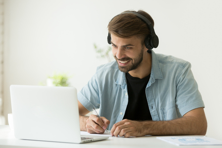 Photo pour Smiling man in headphones looking at computer screen watching webinar, making business video call, young businessman consulting remote client online writing notes, hr holding distance job interview - image libre de droit