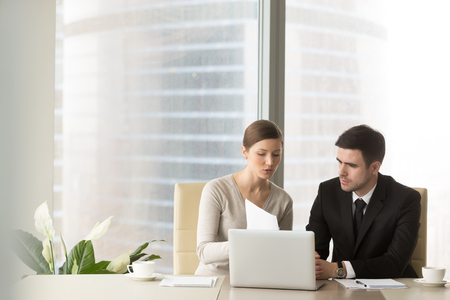 Photo for Millennial businesswoman discussing company indicators with male business partner at meeting in office. Female financial consultant, credit expert explaining terms of contract to client or investor - Royalty Free Image