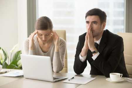 Photo pour Tired stressed businessman and businesswoman sitting at desk and pondering over problem. Difficult negotiations between business partners, lack of understanding among colleagues, difficulties in work - image libre de droit