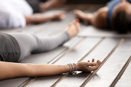Group of young sporty people practicing yoga, lying in Corpse pose, Savasana exercise, working out, resting after practice, female hand with wrist bracelets close up, studio. Healthy lifestyle concept