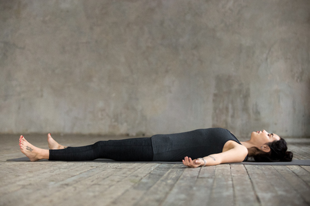 Photo pour Young sporty woman practicing yoga, lying in Dead Body or Corpse pose, Savasana exercise, working out, resting after practice, indoor full length, gray wall in yoga studio - image libre de droit