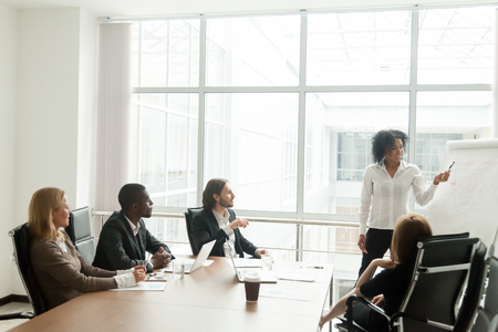 Photo pour African-american businesswoman gives presentation to diverse colleagues at meeting, black manager presenting new plan for project team in boardroom, office worker explains business idea on flipchart - image libre de droit