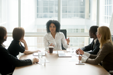 Foto de Black female boss leading corporate multiracial team meeting talking to diverse businesspeople, african american woman executive discussing project plan at group multi-ethnic briefing in boardroom - Imagen libre de derechos