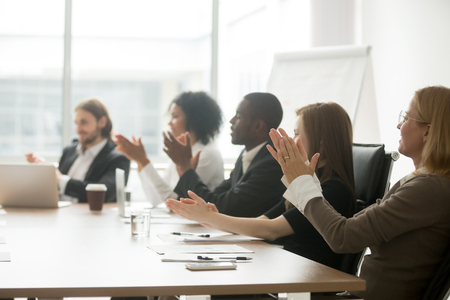 Photo for Multiracial business people applauding sitting at conference table, diverse team clapping hands after group meeting, multinational grateful audience cheering appreciating presentation or training - Royalty Free Image