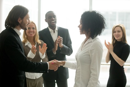 Foto de Grateful boss handshaking promoting african businesswoman congratulating with career achievement while colleagues applauding cheering successful worker, appreciation handshake, employee recognition - Imagen libre de derechos