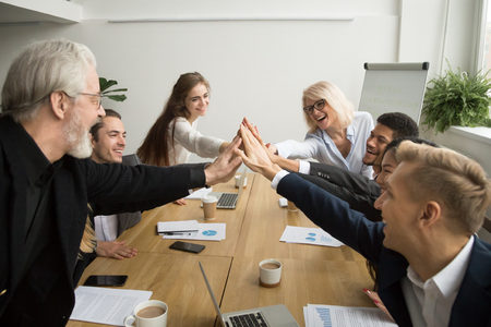 Foto de Diverse young and senior business people giving high five building successful team at meeting, motivated multiracial group of different age uniting celebrating win promising support help in teamwork - Imagen libre de derechos