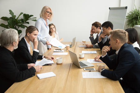 Foto de Dissatisfied senior woman boss scolding employees for bad work at diverse group meeting, angry female executive team leader reprimanding subordinates for poor financial result at office briefing - Imagen libre de derechos