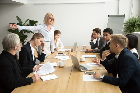 Foto de Angry senior woman boss firing unprofessional employee with hand gesture at diverse team meeting, dissatisfied aged female executive dismissing incompetent manager for bad work result in boardroom - Imagen libre de derechos