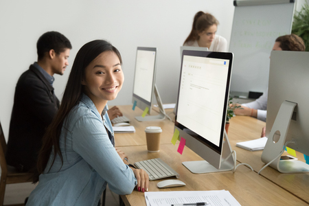 Photo pour Smiling asian office employee looking at camera working with multiracial colleagues, happy young company manager sitting at corporate workplace, cheerful team member posing with desktop computer - image libre de droit