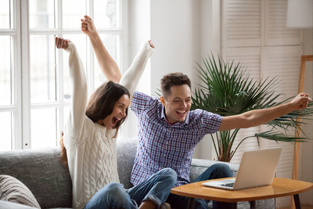 Foto de Excited man and woman screaming with joy raising hands looking at laptop screen sitting on sofa at home, happy young couple celebrate online win victory, goal achievement, good news, new opportunity - Imagen libre de derechos