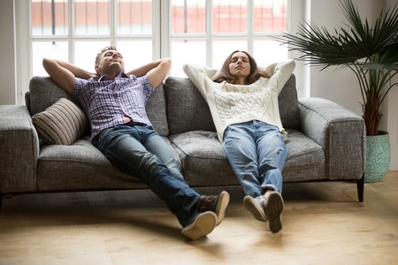 Young couple relaxing having nap or breathing fresh air, relaxed man and woman enjoying rest on comfortable sofa in living room, happy family leaning on soft couch taking break for dozing together