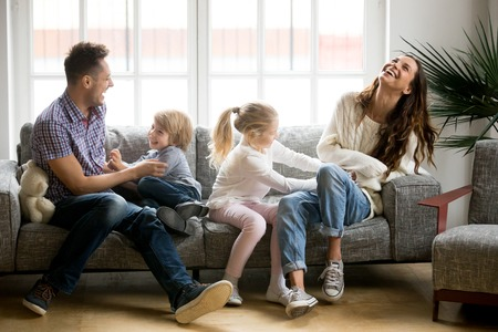 Foto de Happy parents and kids having fun tickling sitting together on sofa, cheerful couple laughing playing game with little active children son and daughter in living room at home, family funny activity - Imagen libre de derechos