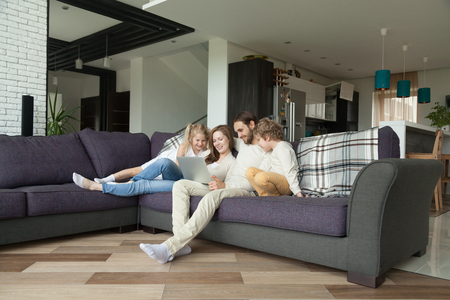 Photo pour Smiling parents with kids having fun with laptop in cozy living room interior, couple with children son and daughter using computer on sofa at home, happy family relaxing together shopping online - image libre de droit