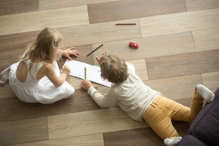 Foto de Kids sister and brother playing drawing together on wooden warm floor in living room, creative children boy and girl having fun at home, siblings friendship, underfloor heating concept, top view - Imagen libre de derechos