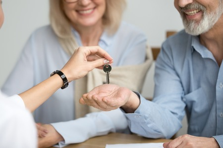 Photo pour Realtor giving senior aged couple key to new house at meeting, happy older real estate owners make purchase deal concept, smiling elderly family bought or rented apartment, close up view of hands - image libre de droit