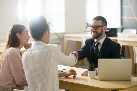 Foto de Smiling lawyer, realtor or financial advisor handshaking young couple thanking for advice, insurance broker or bank worker and millennial customers shake hands making deal, investment or taking loan - Imagen libre de derechos