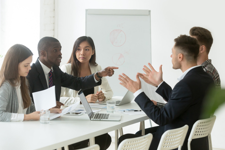 Photo for Diverse employees arguing during team meeting, african office worker disagreeing with caucasian colleague - Royalty Free Image