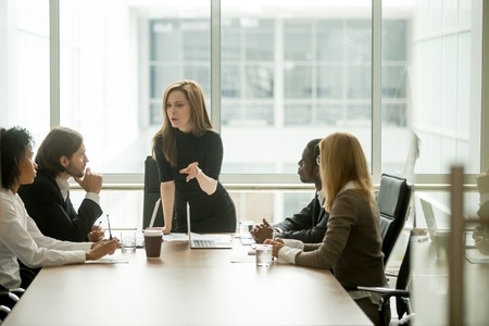 Serious woman boss scolding employees for bad results or discussing important instructions at multiracial team meeting